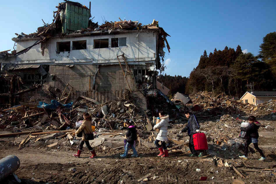 A family of evacuees carry their belongings from their destroyed home in Rikuzentakata, northeastern Japan.