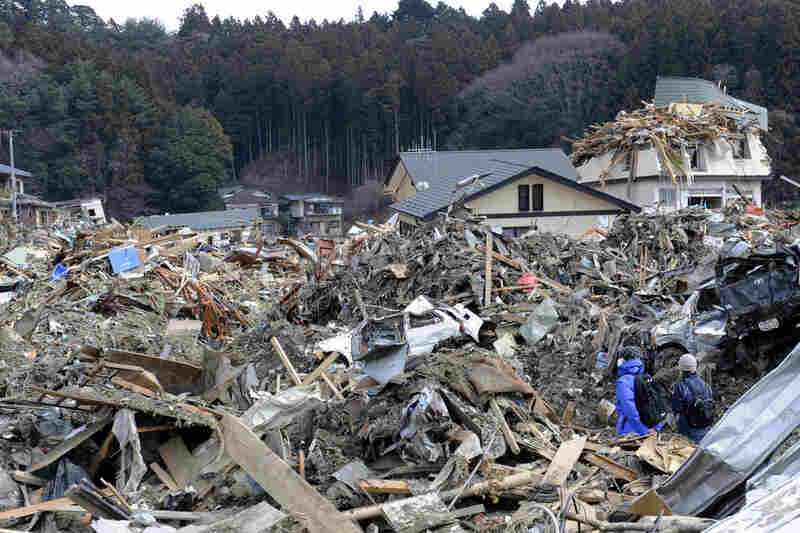 A couple walks among the debris in Rikuzentakata on Tuesday.