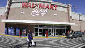 A woman makes her way out of a Wal-Mart store in Oakland, Calif. Wal-Mart Stores Inc. reported a 27 percent increase in fourth-quarter net income as the world's largest retailer benefited from cost-cutting and strong sales overseas.