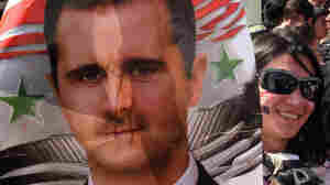 A supporter of Syrian President Bashar Assad carried a poster with his image in Damascus earlier today (March 29,