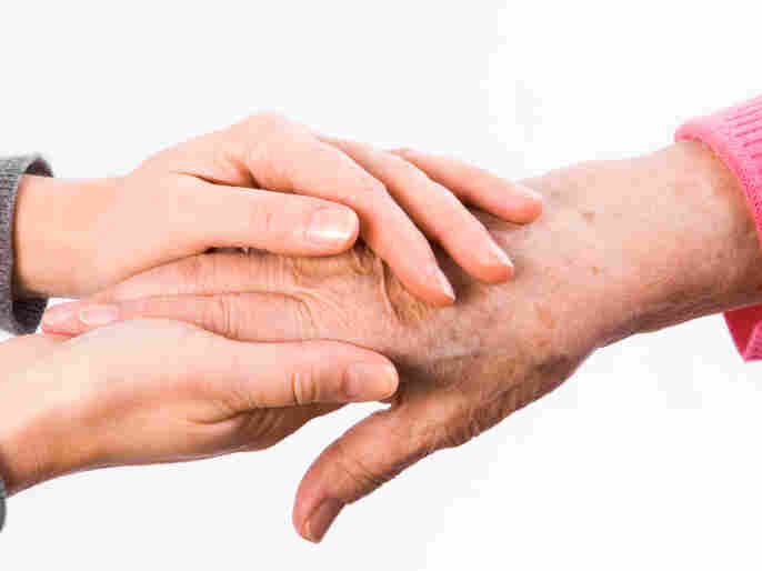 A young woman holds an older woman's hand.