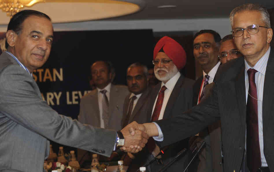 Indian Home Secretary Gopal K Pillai (right) shakes hands with his Pakistani counterpart Chaudhary Qamar Zaman (left) during a bilateral meeting in New Delhi on March 28, 2011.