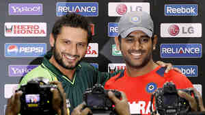"""Pakistani captain Shahid Afridi (left) and India's captain, Mahendra Singh Dhoni, at a news conference in Mohali, India, on Tuesday. The two men and their teams will face off Wednesday in a World Cup semifinal that is being dubbed """"the mother of all matches."""""""
