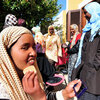 A young  African woman who fled Libya puts on makeup as she rests with other female refugees Monday on the tiny Italian island of  Linosa.