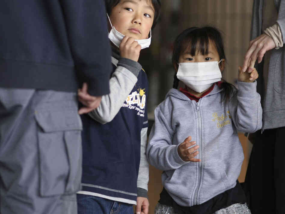 Children watch as their father is screened for radiation at a shelter in Fukushima prefecture, Japan. Plutonium is seeping from a damaged nuclear power plant into the soil outside, officials said Tuesday.