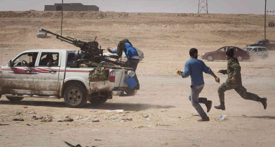 Libyan rebels flee as Moammar Gadhafi's forces fire at them on the front lines outside Bin Jawad, east of Sirte, on Tuesday.