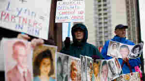 Catherine Coleman Murphy, of Lansdale, Pa., and Jack Wintermyer, of Silver Spring, Md., protest outside Cathedral Basilica of Saints Peter and Paul in Philadelphia the day after the Philadelphia archdiocese suspended 21 priests who were named by a grand jury as child molestation suspects.