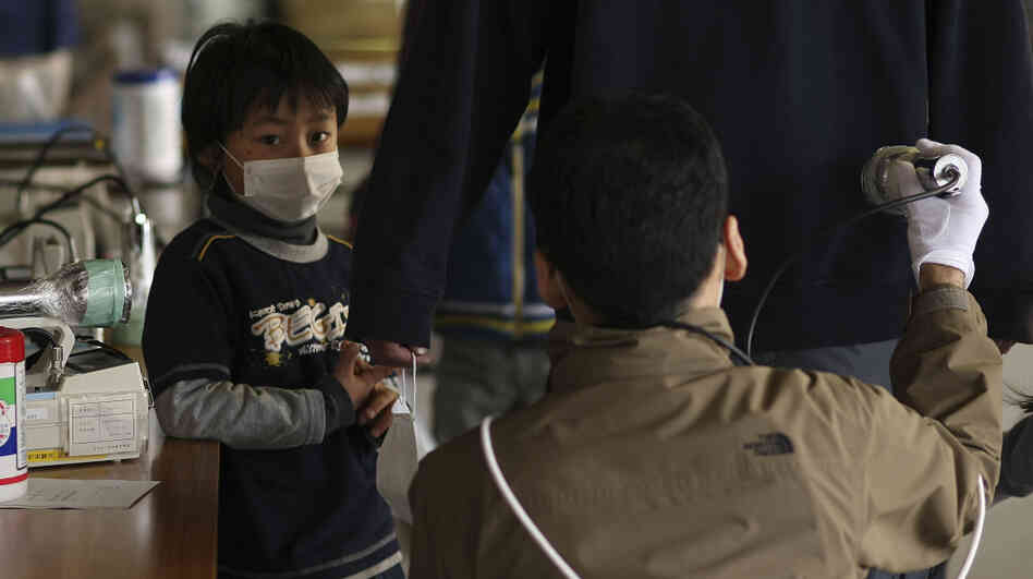 Earlier today (March 29, 2011), a boy watched his father being screened for radiation at a shelter in Fukushima prefecture.