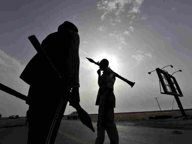 Libyan rebels carry rocket-propelled grenades as they take position at the west gate of the eastern city of Ajdabiya on Wednesday.