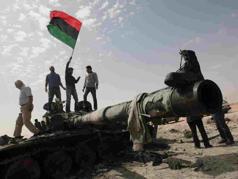 Libyan rebels wave a flag as they celebrate on a destroyed tank east of Tripoli on March 29, as meanwhile international powers gathered in London to map out a post-Gadhafi future for Libya. Some worry that the current U.S. action in Libya could have more far-flung implications.