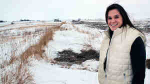 Betsy  Dahl stands on the 180 acres of land that she farms for Helen Gunderson, which  she is converting to organic. Dahl is one of a growing number of young women  getting into farming.