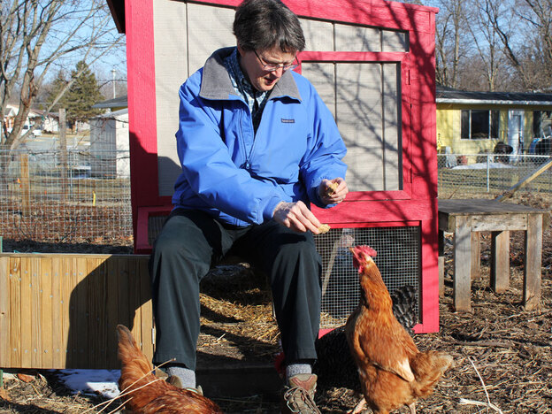 "Helen  Gunderson sits with her chickens by their ""summer home"" coop in her garden. The  eggs are for her personal use, but Gunderson is a farmer by trade, managing 180  acres of her own land in Rolfe, Iowa."