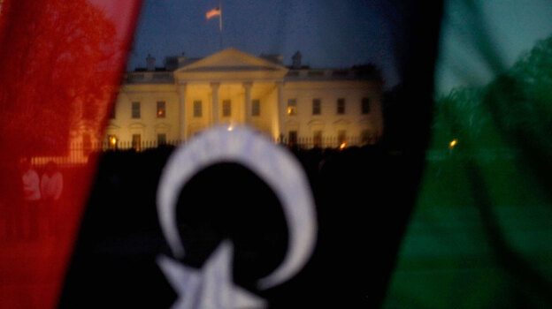 A demonstrator holds up a pre-Gadhafi Libyan flag while standing vigil in front of the White House on March 28. (Getty Images)