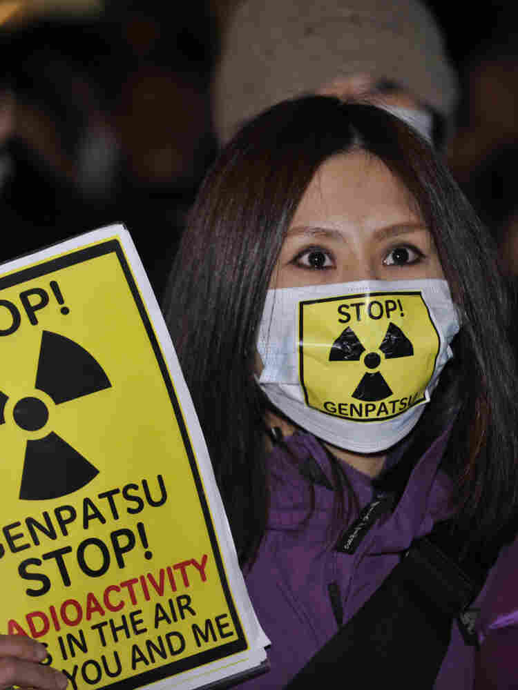 A Japanese civic group member holds a placard to protest against Tokyo Electric Power Co. on  March 30.