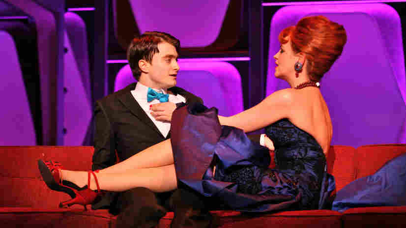 Not a toy: J. Pierrepont Finch (Daniel Radcliffe, left) is an ex-window washer climbing the corporate ladder at the World Wide Wicket Company — where the seductive Hedy LaRue (Tammy Blanchard) is just one of the temptations on the road to success.