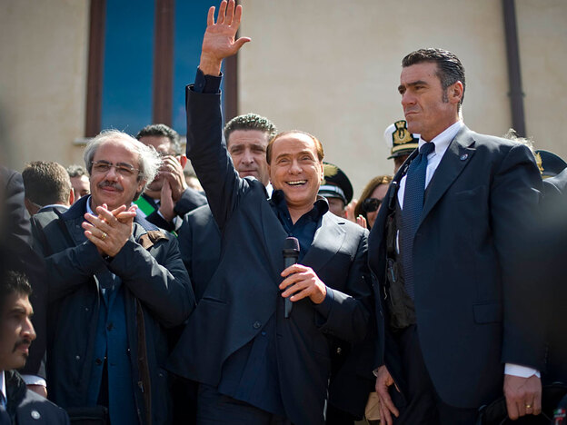 Premier Silvio  Berlusconi salutes as he arrives during his visit to the tiny Italian  island of Lampedusa, on Wednesday, as ships arrived to remove  some of the thousands of North African migrants who have overwhelmed it while  fleeing Libya.