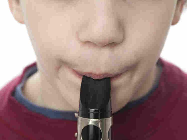 boy plays clarinet.