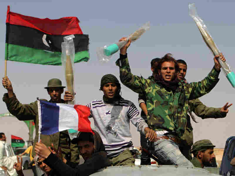 Libyan rebels wave French and rebellion flags as they raise grenades they took from abandoned ammunition stocks of pro-Gadhafi forces. There have been reports that indicate the presence of al-Qaida supporters among the anti-Gadhafi rebels.