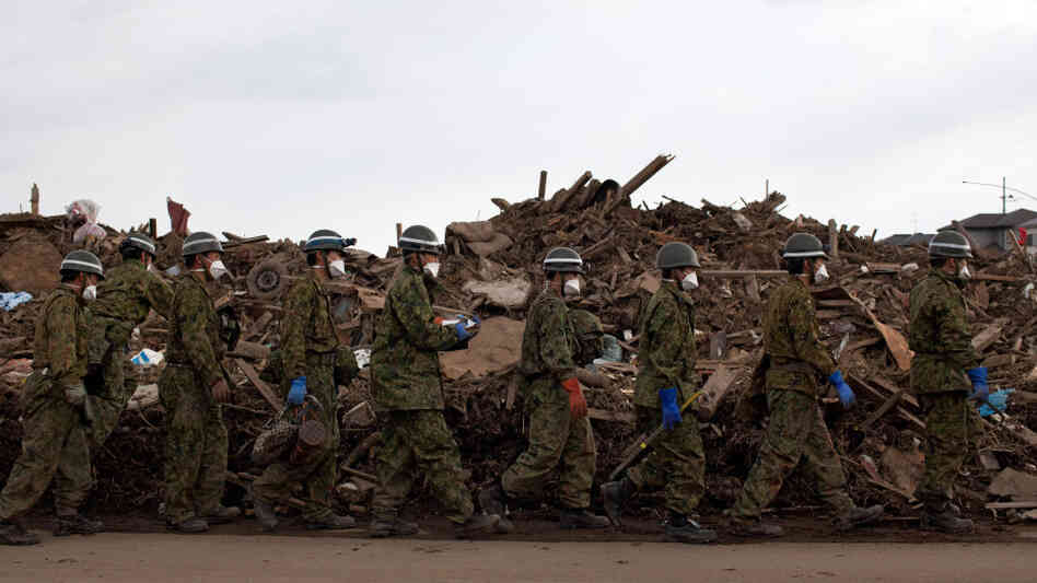 Japanese Self-Defense Force soldiers walked in a line after finding the body of a boy in the rubble in Higashimatsushima, Miyagi prefecture earlier today (March 31, 2011).