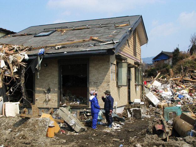 Noriaki Osaka (right) and his brother, Toshiaki, stand by the home where they found and removed the bodies of their sister and  100-year-old mother in Rikuzentakata.