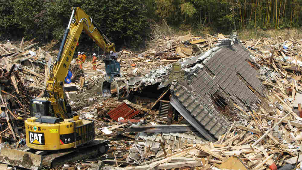 Firefighters use heavy equipment to  tear apart a collapsed 300-year-old house while searching for the dead in the rubble  of Rikuzentakata, Japan.