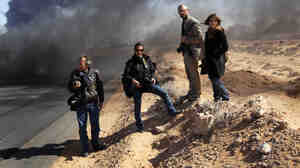 Ras Lanuf, March 11: Lynsey Addario and Tyler Hicks of The New York Times (center left and right) stand on the side of a road in Libya with Yuri Kosyrev of Time magazine and freelancer Nicki Sobecki. Four days later, Addario and Hicks were taken captive along with Times journalists Anthony Shadid and Stephen Farrell.