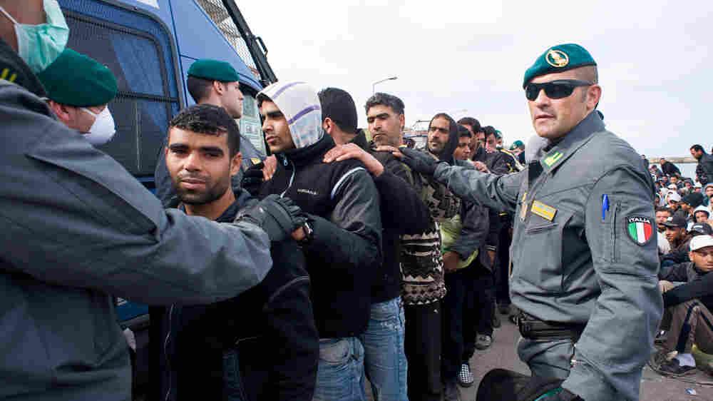 Italian  customs policemen escort migrants in Lampedusa, Italy, on Wednesday.