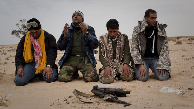 Libyan rebels pray in the desert on the front lines near the town of Sultan, south of Benghazi. (AP)