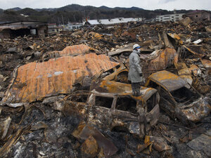 KESENNUMA, JAPAN - MARCH 16:  A rescue worker stands on top of a burned vehicle looking for more bodies hidden amongst the rubble of a village destroyed by the devastating earthquake, fires and tsunami.