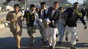 Afghans carrying a man who was wounded in an attack on the U.N.'s Mazar-i-Sharif office during a demonstration to condemn the burning of the Quran by a Florida pastor.