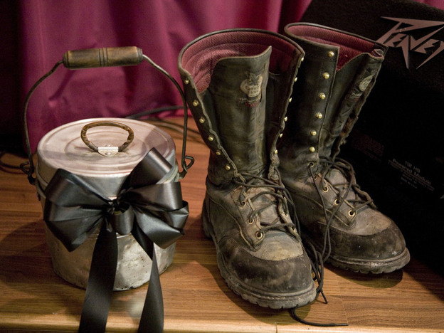 Coal miner boots and a lunch pail sat on the stage of the New Life Assembly church in Whitesville, W.Va., last April 11 during a Sunday service dedicated to the memory of the miners who were killed. (Getty Images)