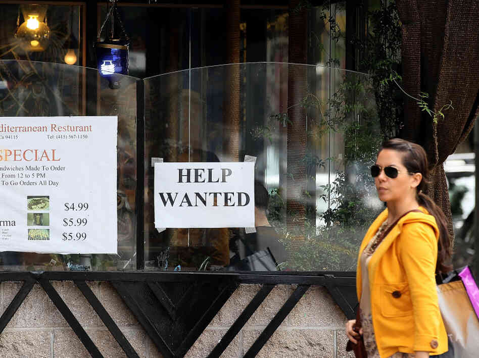 "A woman walks by a ""Help Wanted"" sign taped to the window of a restaurant in San Francisco. Some employers are refusing to consider hiring anyone who doesn't already have a job, leading t"