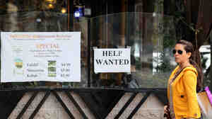 "A woman walks by a ""Help Wanted"" sign taped to the window of a restaurant in San Francisco. Some employers are refusing to consider hiring anyone who doesn't already have a job, leading to increased scrutiny by the EEOC."