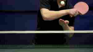 A man playing table tennis about to serve the ping pong ball.