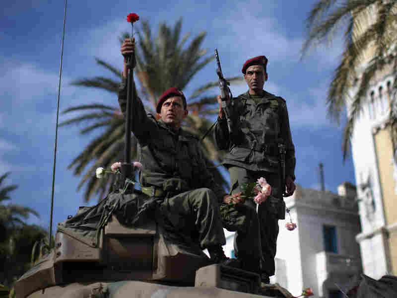 A Tunisian soldier arranges flowers on his tank on Jan. 21 in Tunis.
