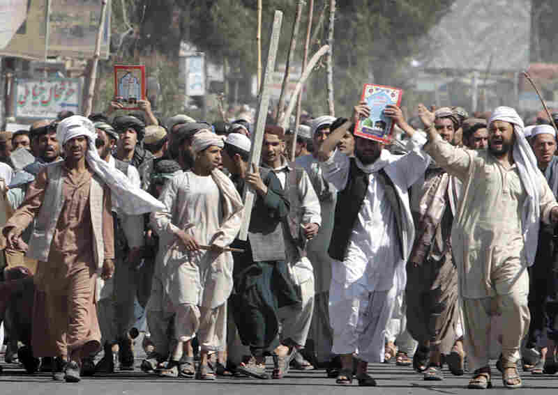 Afghan protesters hold copies of the Quran as they march during a demonstration to condemn the burning of a copy of the Muslim holy book by a Florida pastor, in Kandahar, Afghanistan, on Saturday.