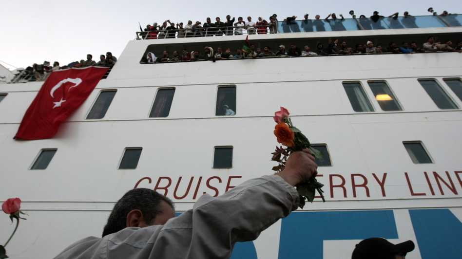 Libyans in Benghazi hold up flowers to welcome the Turkish ship evacuating the wounded from Misurata.