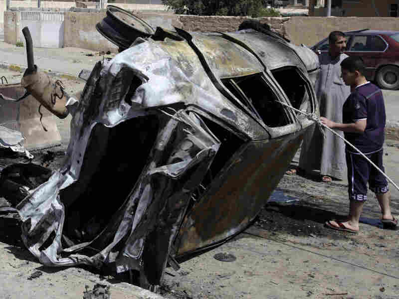 People inspect a destroyed car in front of a provincial council building in Tikrit, 80 miles north of Baghdad, on Wednesday. A small squad of insurgents attacked the building Tuesday, leaving 57 people dead.