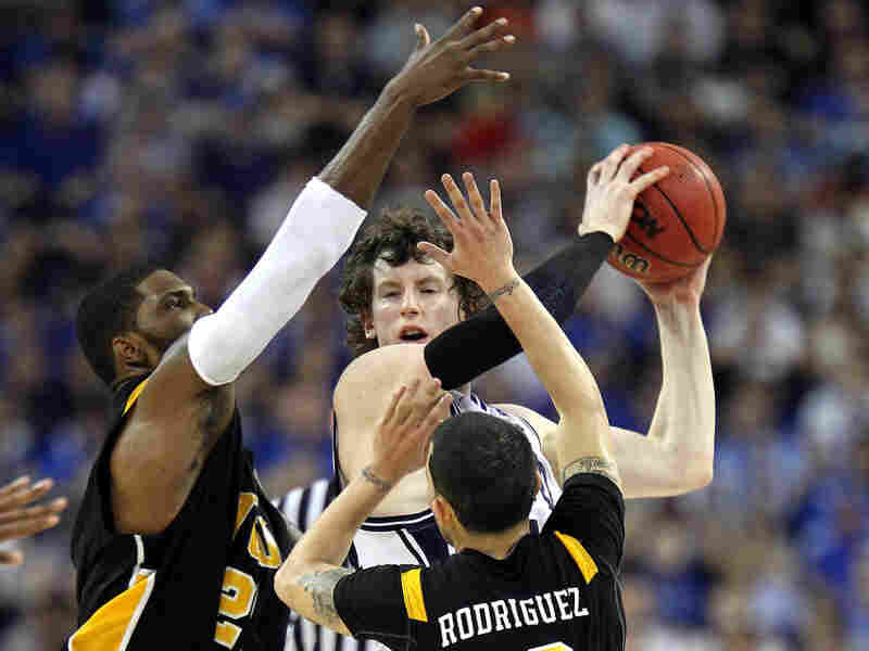 Matt Howard (center) of the Butler Bulldogs handles the ball against Jamie Skeen (left) and Joey Rodriguez of the Virginia Commonwealth Rams during the National Semifinal game of the 2011 NCAA Division I Men's Basketball Championship at Reliant Stadium on April 2 in Houston.