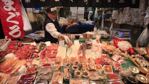 A Tokyo tuna wholesaler adds slices of fish to his stall on March 23. Fish prices have plummeted in Japan amid fears that radioactive material leaking from the damaged Fukushima Dai-ichi nuclear power plant may have contaminated the animals. But experts say there's no risk right now and that fish is safe to eat. (AP)