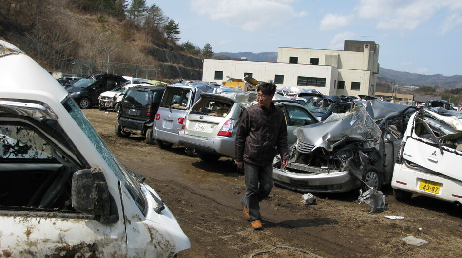 "Mitsuyuki Yagi looks for his Toyota sedan in a ""graveyard"" on the outskirts of Miyako city. He hopes to be able to retrieve his house keys and computer."