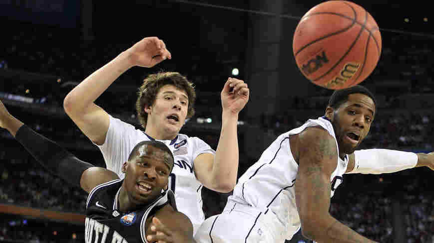 Shelvin Mack of the Butler Bulldogs fights for the ball against Tyler Olander and Alex Oriakhi of the Connecticut Huskies during the National Championship Game.