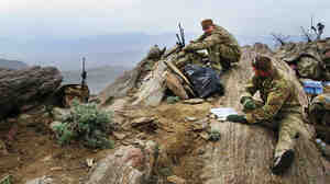 Lt.  Col. Brian Filler (left) and Tech. Sgt. John Oliver watch over the Galuch Valley  from the top of a mountain in Laghman province in eastern  Afghanistan on March 27. They are part of a team of Joint Terminal  Attack Controllers for the U.S. Air Force, traveling on the ground with combat  troops and coordinating with aircraft to reduce the likelihood of airstrike  errors.