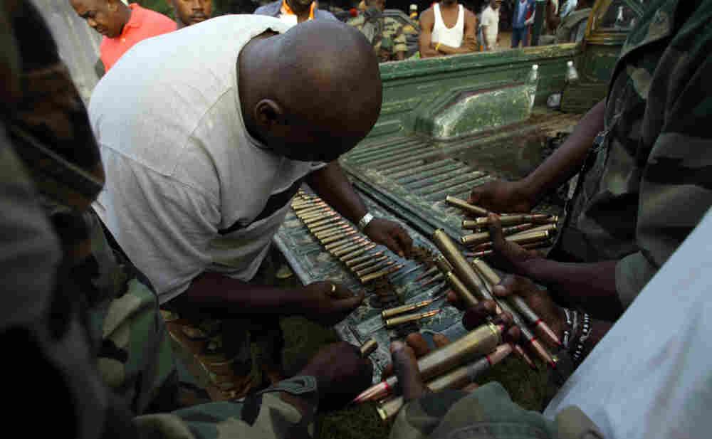 Fighters loyal to Alassane Ouattara prepare ammunition in Abidjan on April 3, 2011.