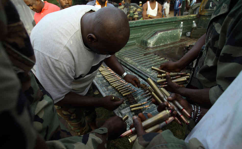 Fighters loyal to Alassane Ouattara prepare ammunition in Abidjan on April 3, 2011.