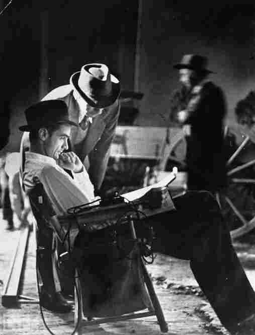Hughes studies the script as he sits on the set of The Outlaw.