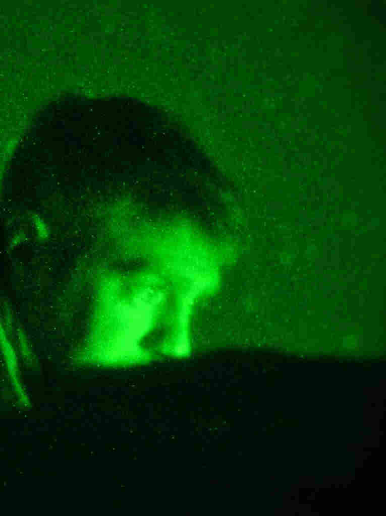In the  middle of the night, Tech. Sgt. John Oliver watches a video monitor and  communicates with pilots thousands of feet overhead.