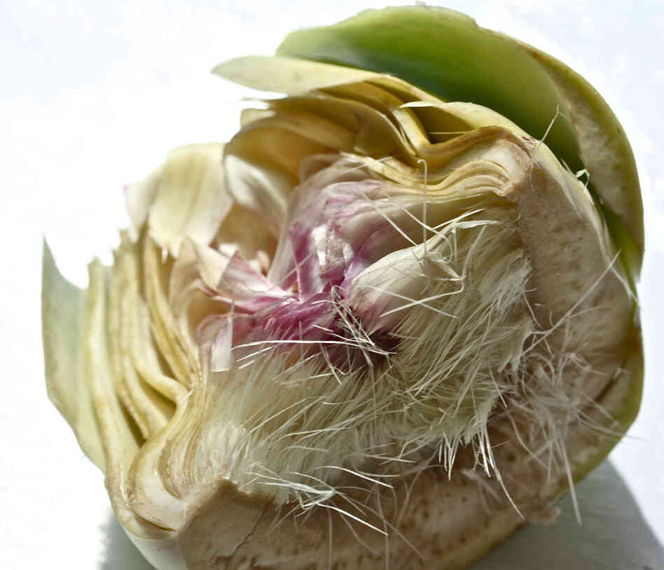 An artichoke sliced in half, exposing the fuzzy choke