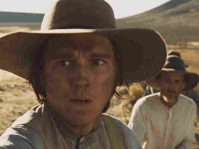 The settlers' party also includes Thomas Gately (Paul Dano, left) and William White (Neal Huff), who struggle to decide whether Bruce Greenwood's Meek is trustworthy.