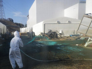 TEPCO workers spray synthetic resin over the ground at the plant to prevent radioactive dust from spreading beyond the premises.